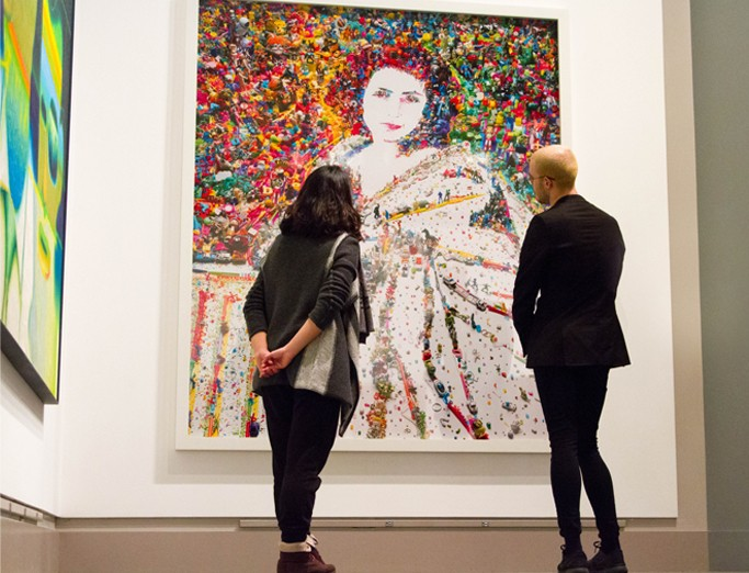 Two people standing in front of a large portrait of a woman with bright colorful pops of color and texture creating the backdrop of the piece, located in the Palmer Museum of Art.