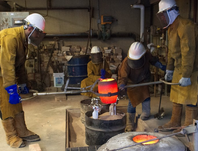 SoVA students in protective clothing and headgear pouring metal into a mold.
