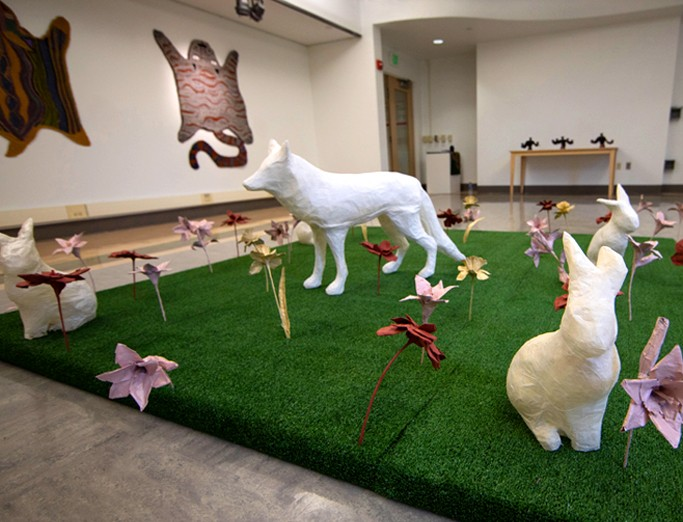 Installation created by Ryan Lawson, showcasing a wolf, rabbit and other animals and colorful flowers on a platform of artificial turf.