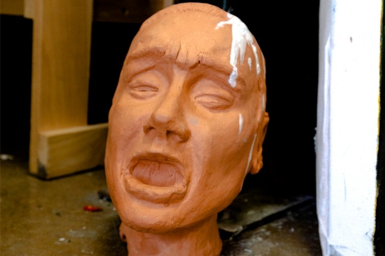 A sculpted head made out of clay sitting on the floor in the SoVA Ceramics Studio.