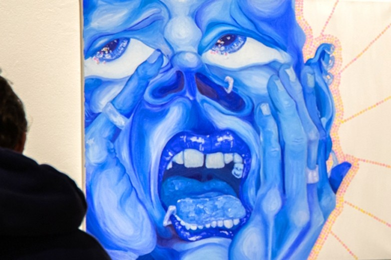 A large scale painting of a face in distraught in different shades of vibrant blue diplayed in the undergraduate juried show at Zoller Gallery.