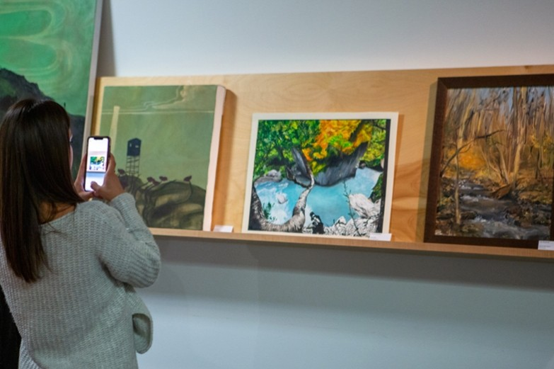 A student taking a photo from her phone of a display of matted artwork on a shelf at the Palmer Museum of Art.