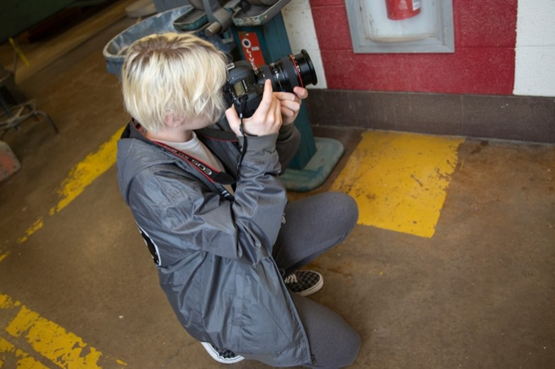 A student kneeling on the floor taking a photograph of students working in the SoVA Wood & Metal Shop.