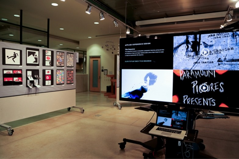 Undergraduate graphic design student work exhibition: showcasing digital designs and video on a flat-screen TV, and various logo and poster designs pinned up on a divider board on casters.
