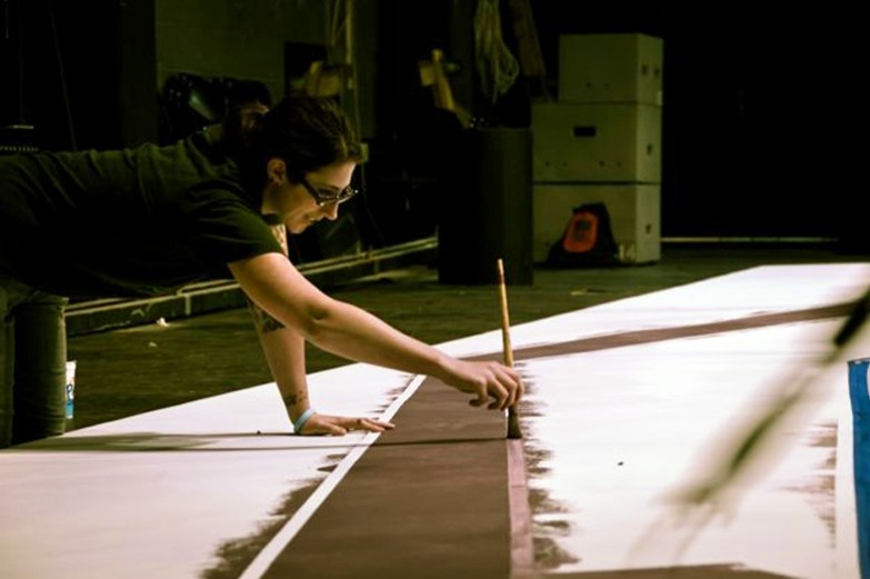 A student painting a long brushstroke across a scenic backdrop at the Theatre Arts Production Studio.