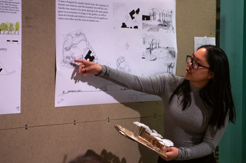 During a critique, a first-year landscape architecture student explains and points to a section of a poster while holding her 3d model.