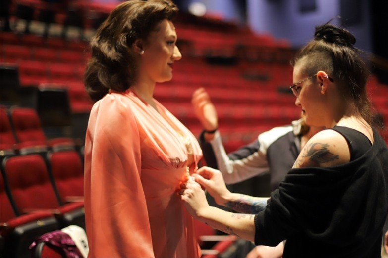 A student fixing the front clasp of a student actor's costume during a rehearsal break of the musical play Kiss of the Spider Woman.