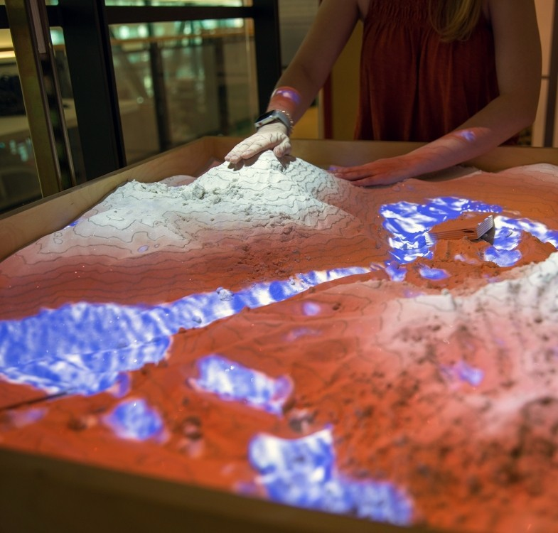 A student patting the top of sand in a sandbox with an overhead projection effect of contour lines and water effect reflecting on the sand during a landscape architecture student display event.