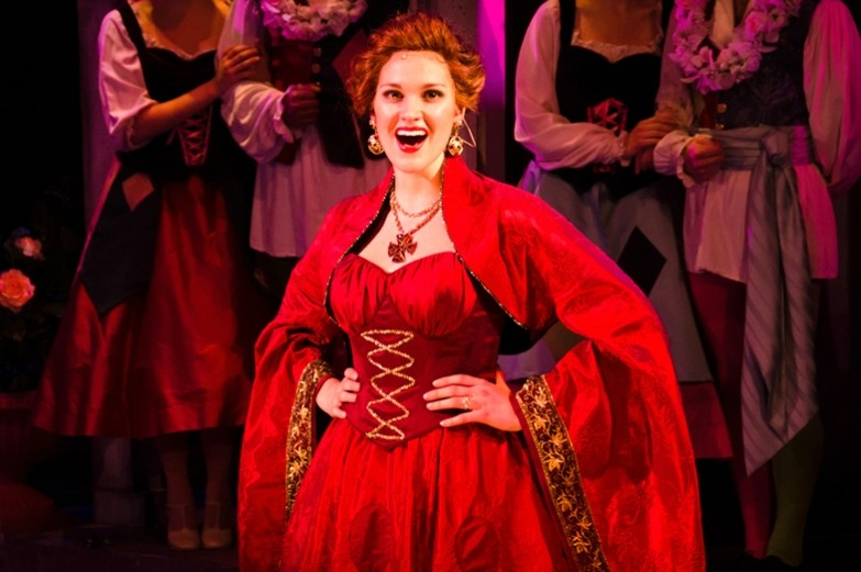 A female actress dressed in a beautiful red dress with gold trim stands center stage singing a musical number from the production of Kiss Me Kate.