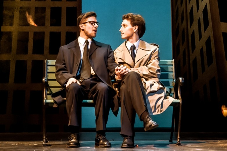 A scene from the production of Angels in America where two actors are sitting on a city park bench talking and holding hands. Performed in the Playhouse Theatre at the University Park campus.