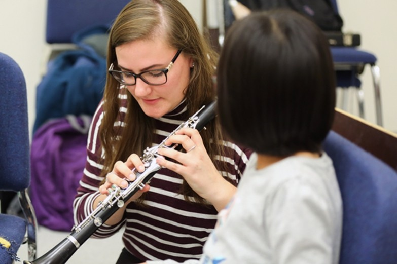 A student from the School of Music Ed program, helping an elementary student with her clarinet.