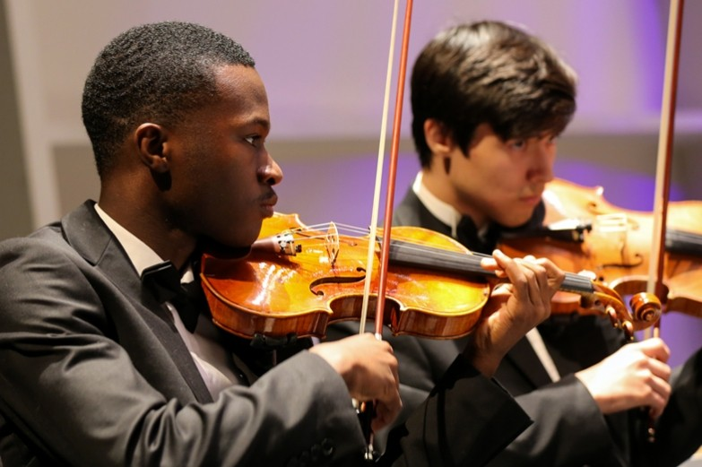 School of Music students dressed in tuxedos are playing their violins during a Mosaic performance.