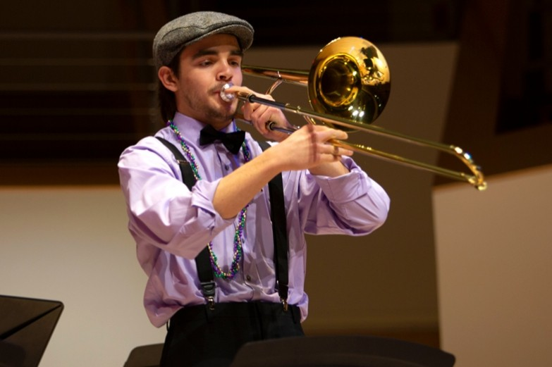 School of Music student playing his trombone on stage during the Mardi Gras Jazz Concert at the Recital Hall.