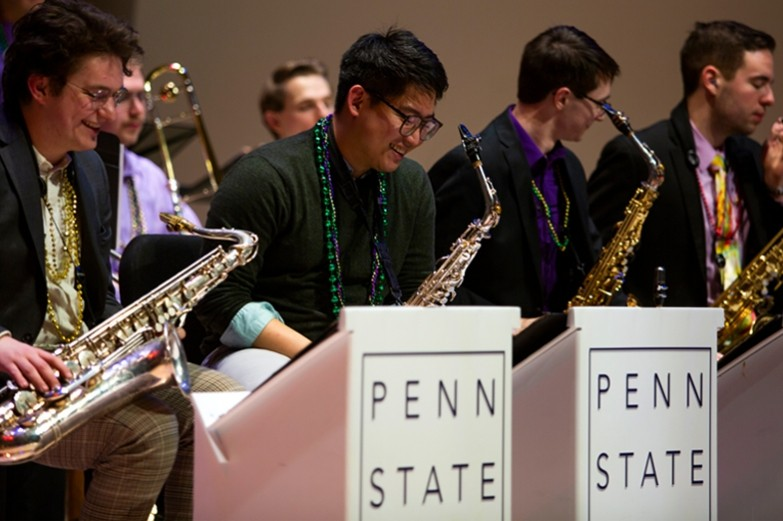 School of Music students playing their saxophones on stage during the Mardi Gras Jazz Concert at the Recital Hall.