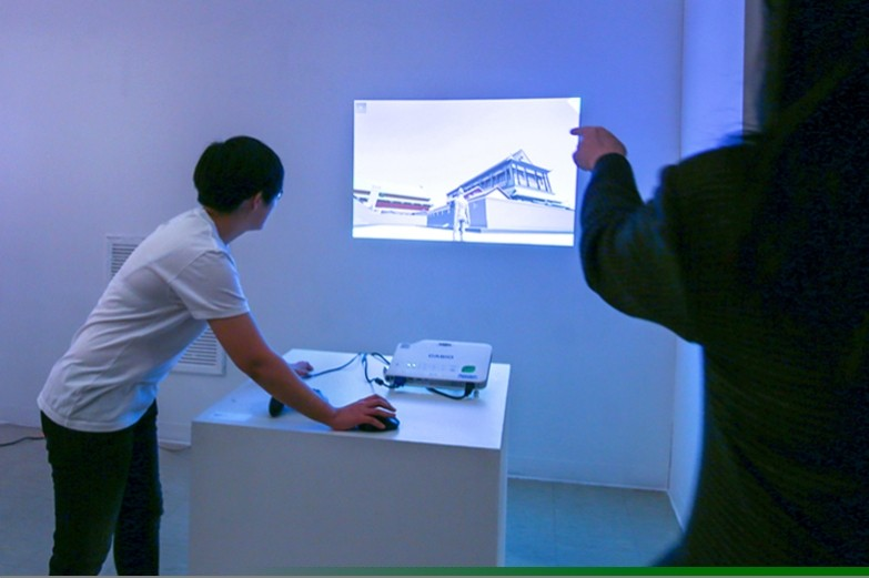 Student using digital projector to display visual presentation on the wall of a blue-light cast room.