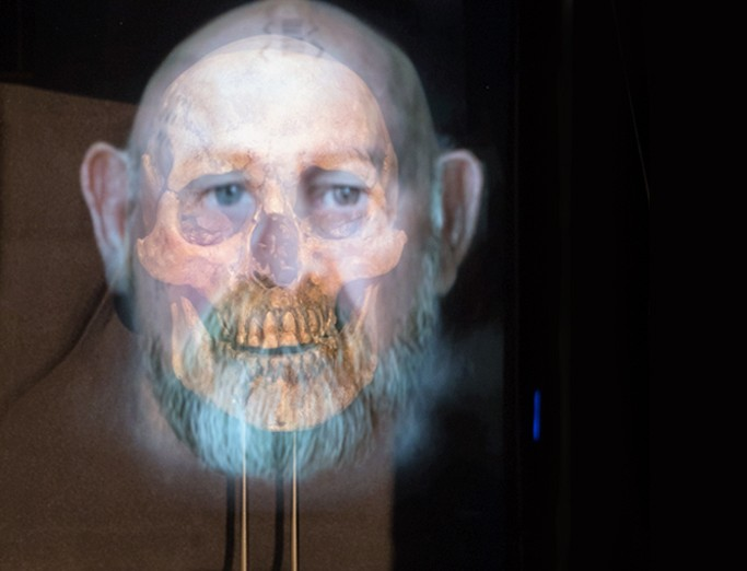 Transparent projection of a man's face and skull image overlaying his face.