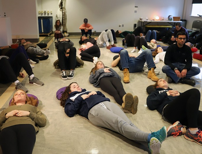An array of students lying peacefully on the floor participating in a Zen Den Mindfulness exercise.