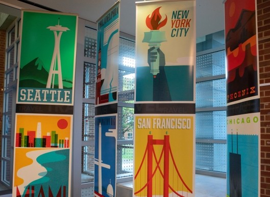 Stacks of colorful design posters of major U.S. cities, hanging from the ceiling.