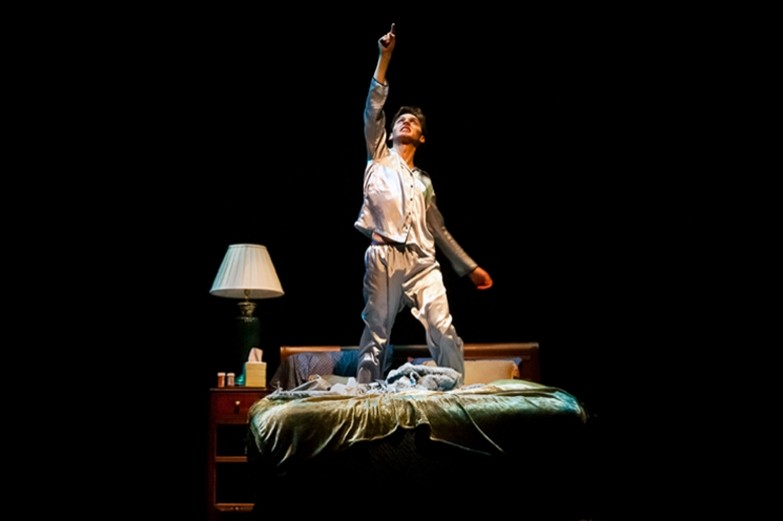 Student theatre performer kneeling on bed on a darkened stage with with arm outstretched overhead.