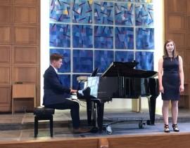 Meghan Nardella singing beside a piano