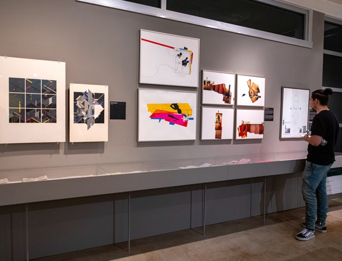 A student looking at various framed artwork displayed along a gallery wall.