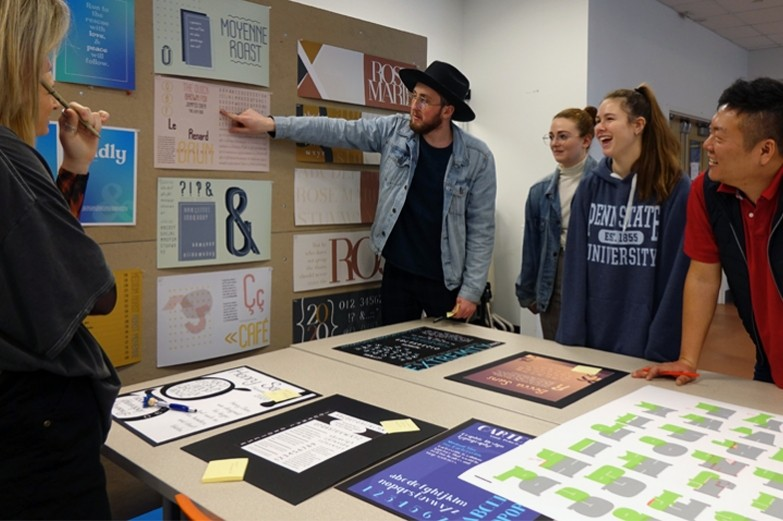 A graphic design student presents his typography work displayed on a wall during studio class.
