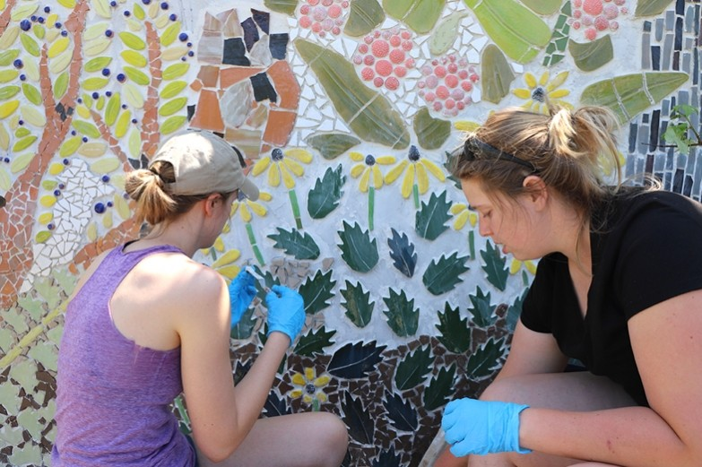 Students work outside on Dani Spewak's Morning Star House Public Art Installation, which showcases bright green leaves and flowers.