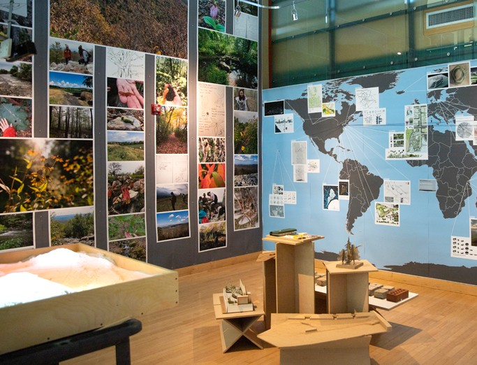 Full wall display of landscape architecture plans created by students, showcasing a rendered map of the world connecting parts of the world to the project renderings with string.
