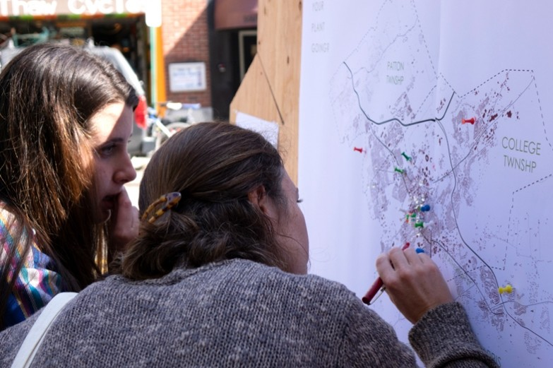 Students find their location on a college township map posted downtown State College during landscape architecture's Parking Day event.