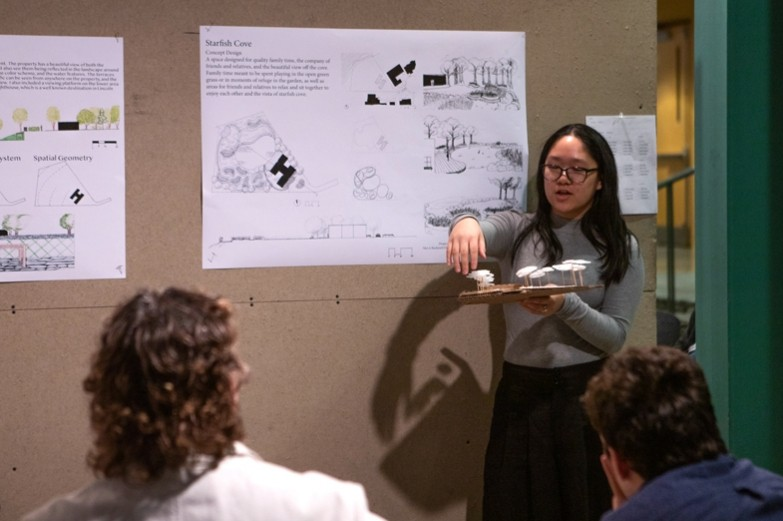 A landscape architecture student explains her project while holding a model during a critique.