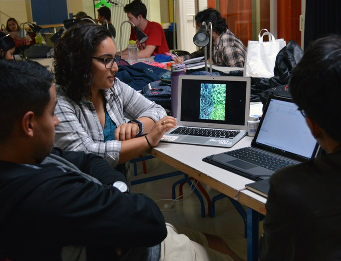 A female student displaying her project on her computer while discussing it with two male students.
