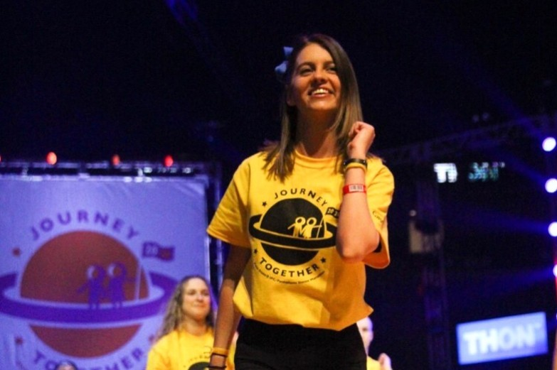 College of Arts and Architecture student performing the Thon line dance on stage in the Bryce Jordan Center.