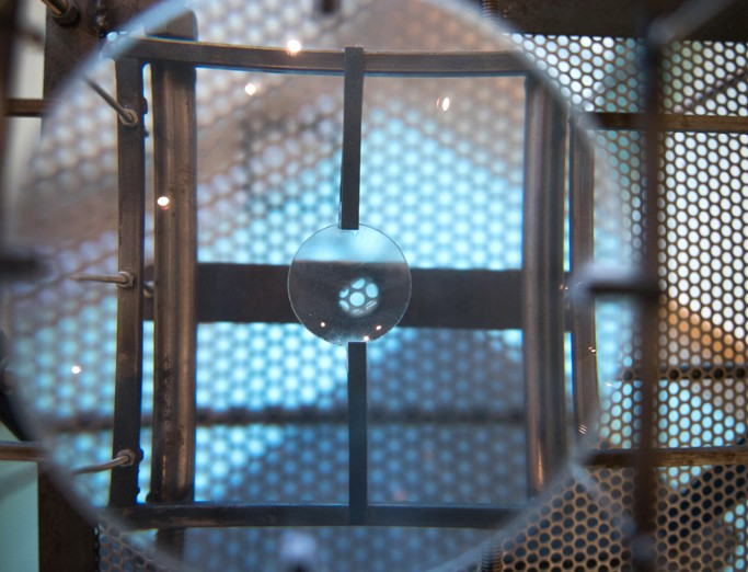 A close up view of a machine project, featuring a cylindrical piece of glass that magnifies the metal framework as you look through it.