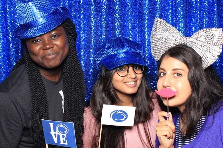 Students pose at the photo booth during Stuckeman's fall welcome back event. Standing in front of a sparkling blue curtain, students can choose fun and silly props to pose with.
