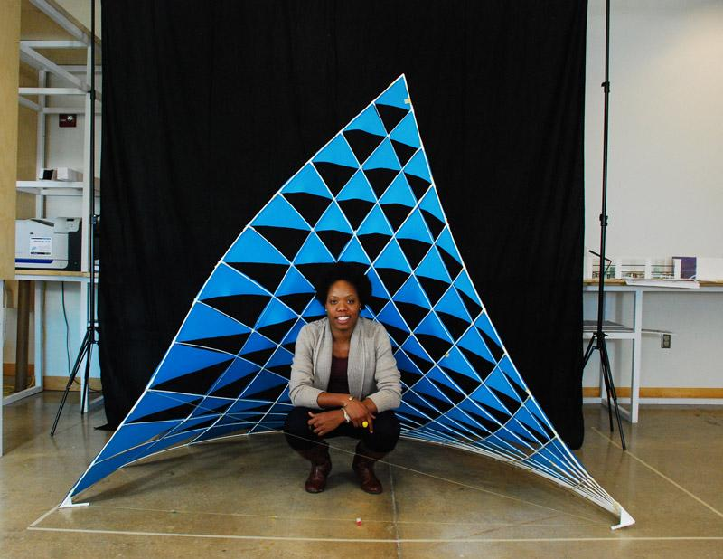 Photo of Vernelle A. A. Noel crouched in front of her self-constructed blue dancing sail sculpture