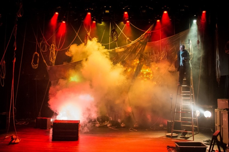 Dramatic stage and lighting design for the play Albatross. A red cast of light permeates the stage with clouds of white smoke surrounding the actor standing on top of a tall ladder.