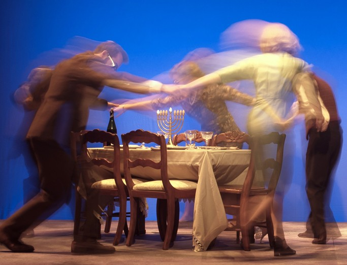 A scene from the musical Caroline, or Change. A group of actors are holding hands dancing around a dinner table during a Chanukah party.
