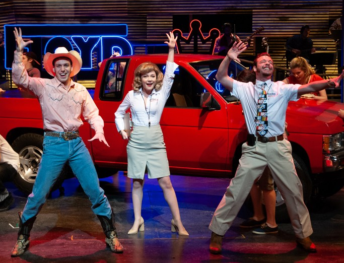 Theatre students dancing and singing in front of a bright red truck with neon lights in the background.