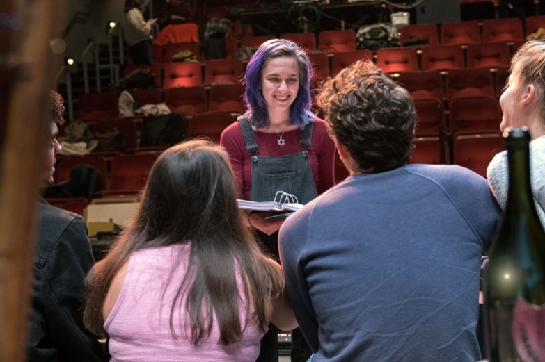 During theatre rehearsal, a stage management student with bright purple hair discusses the next scene with the cast of the Lucky Boy.