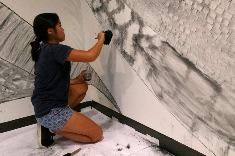 Alec Spangler, assistant professor of landscape design, recruited students, friends and fellow faculty members to help create his massive wall drawing in the Woskob Family Gallery in downtown State College.