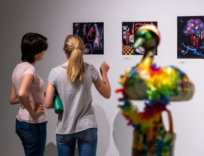 Guests looking at a series of student artwork displayed on a gallery wall during the undergraduate juried show at Zoller Gallery.