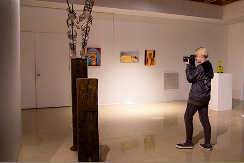 Student photographer poise, shooting artworks included in an undergraduate juried art exhibit in Zoller gallery at Penn State