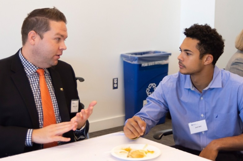 An alumni mentor and student sitting and talking during an A&A mentor lunch event.