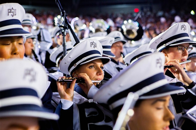 Blue band members play their flutes during a Penn State football night game.