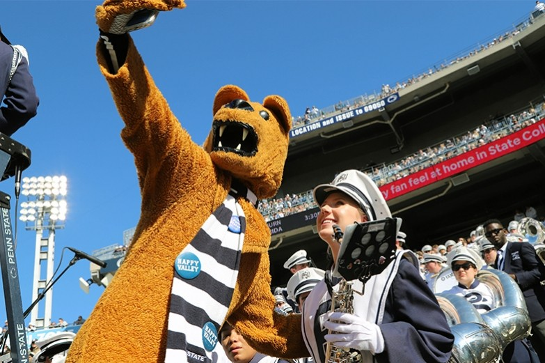 During college game day, a blue band member takes a selfie with the Nittany Lion during the football game.