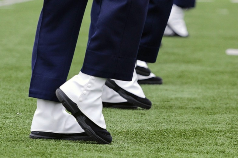 A close up of a row of white spatted band shoes as the blue band marches and performs during a halftime performance.