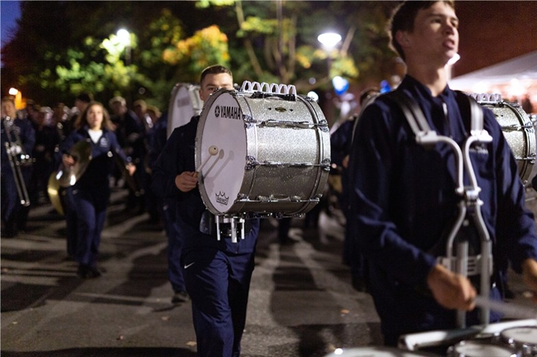 Blue band members march and play their drums during the Penn State homecoming parade.