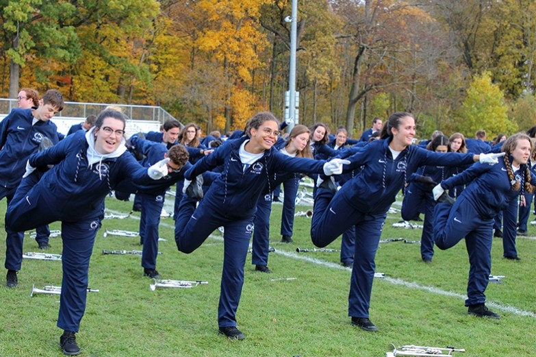 Laughing blue band trumpet players stretch their legs before marching in the homecoming parade.