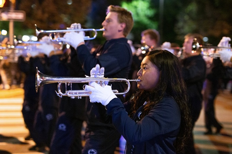 Blue band members march and play their trumpets during the Penn State homecoming parade.