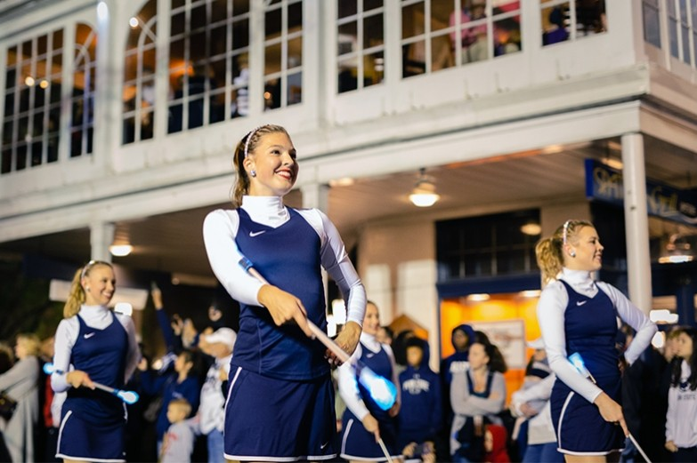 Blue band majorettes perform a routine with lit batons for spectators during the Penn State homecoming parade.